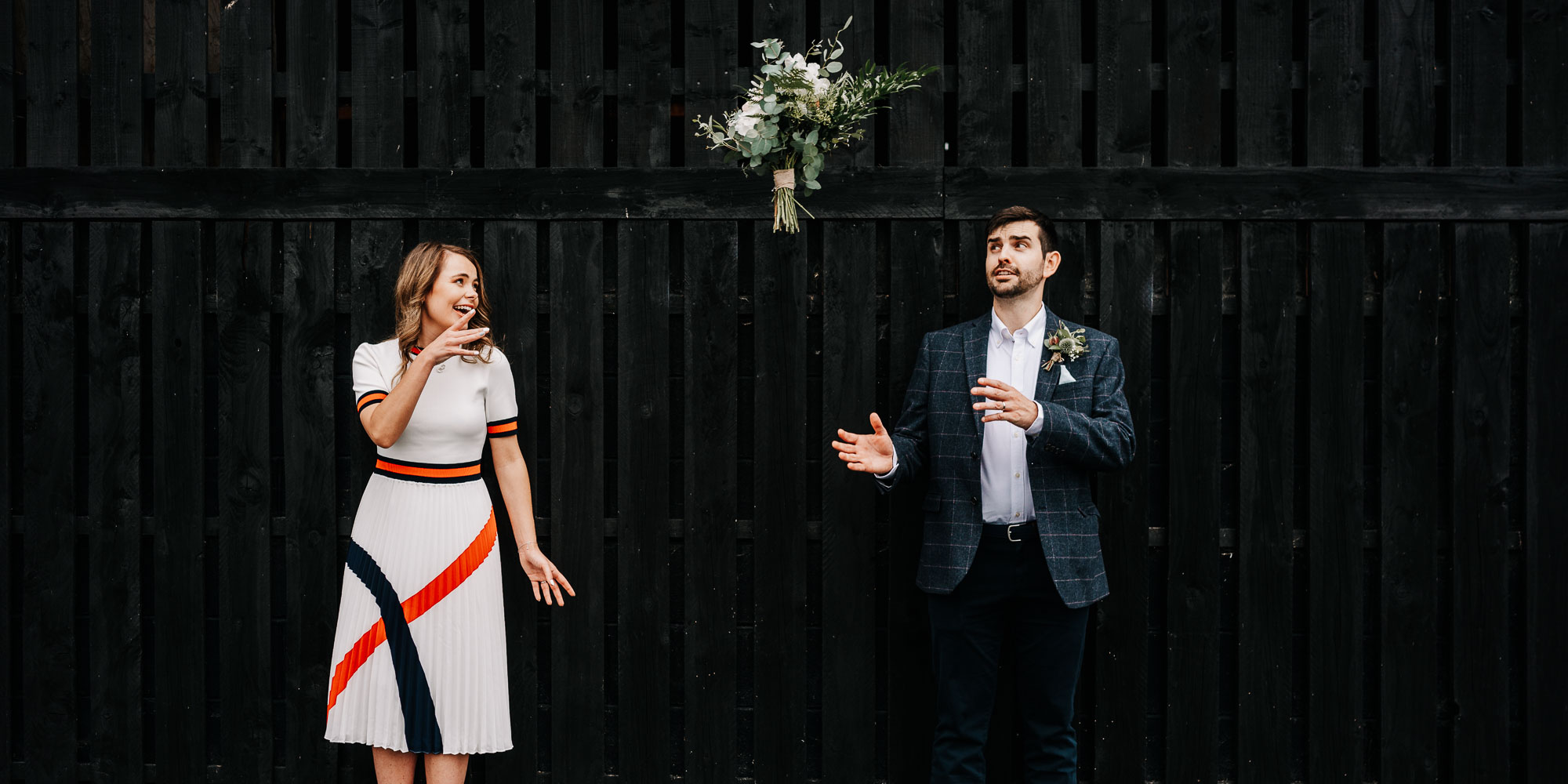 Bride and groom having fun throwing bouquet at each other in front of barn doors