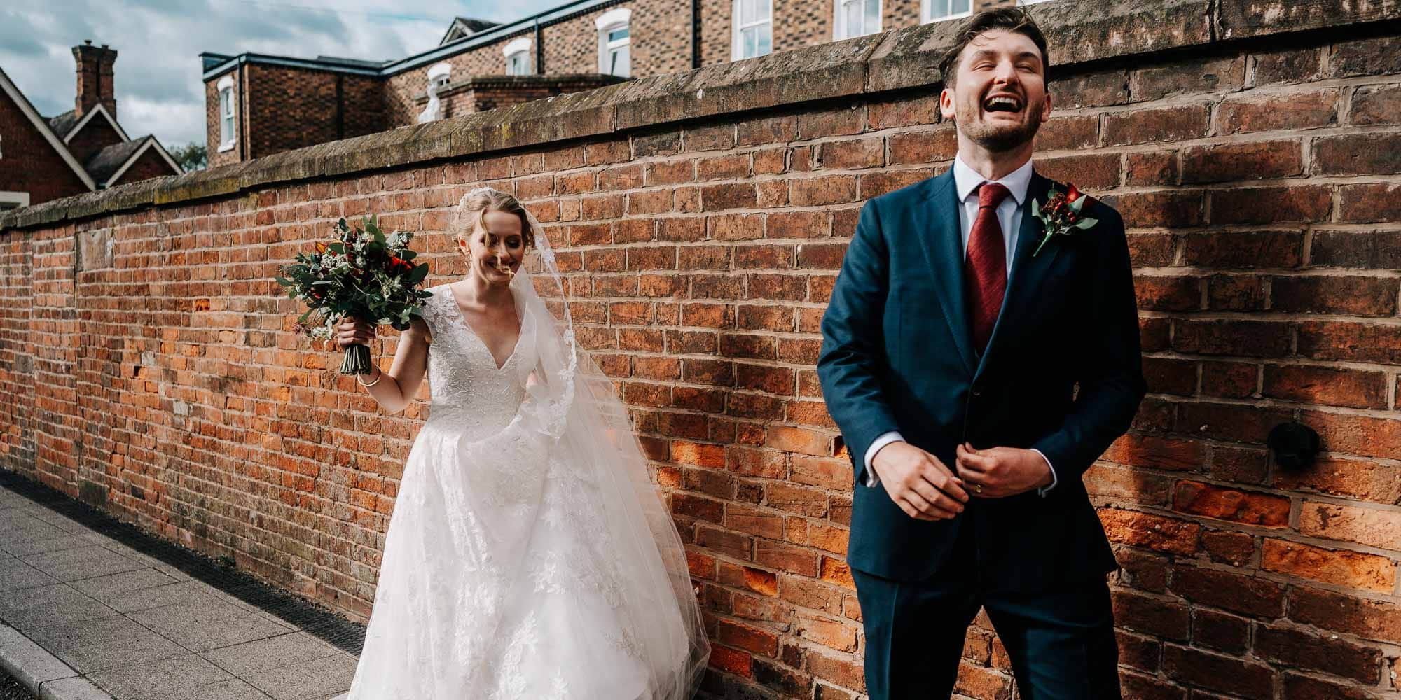 Bride and groom walking along village street laughing at each other