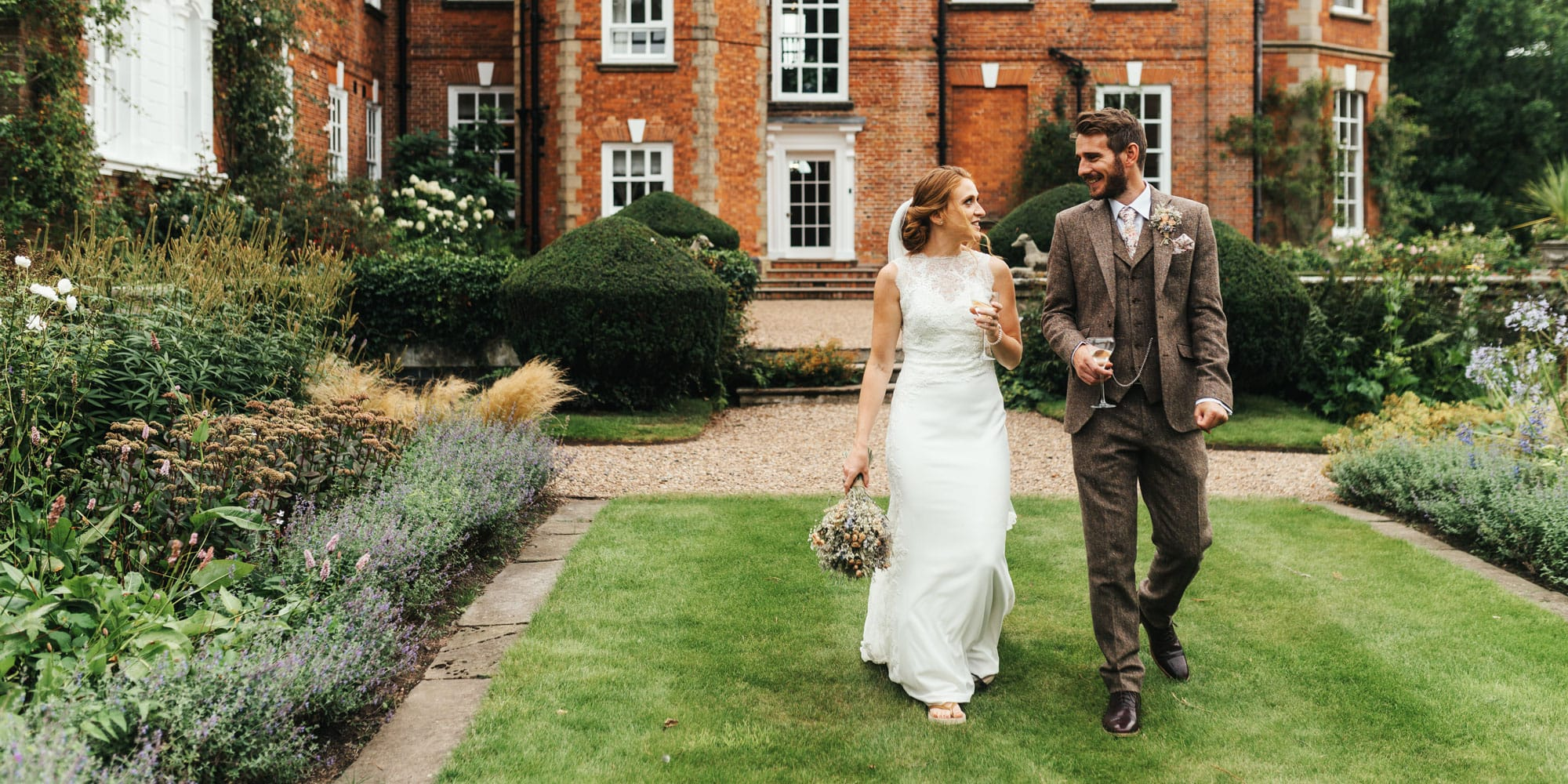 Bride and groom walking with champagne in hand in front of Shropshire stately home