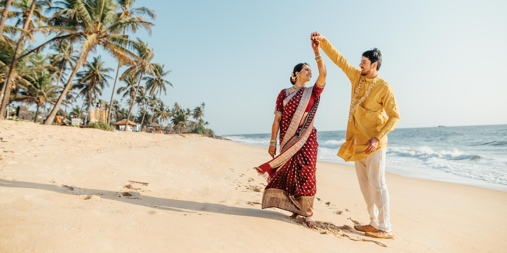 Asian bride and groom dancing on tropical beach in India