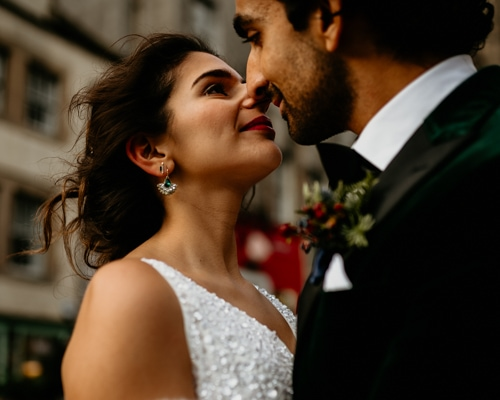 Asian bride and groom in embrace, nearly kissing