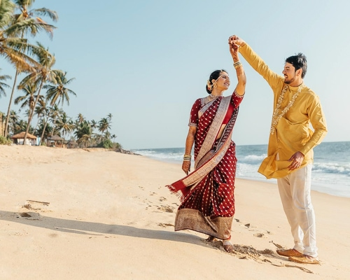 Mixed asian and English couple dancing on an Indian beach
