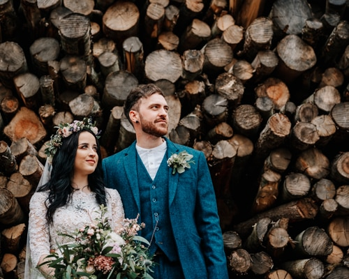 Hipster bride and groom standing in front of log pile
