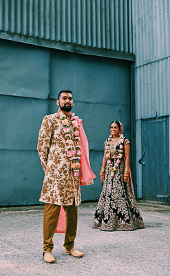 Asian Bride and groom pose for photos in creative industrial barn setting