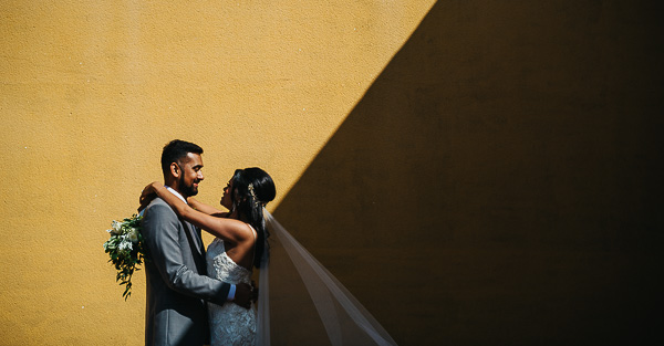 Mediterranean creative wedding photograph showing bride and groom embracing against yellow wall with hard shadow