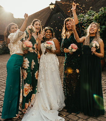 Asian bride and bridesmaids in green dresses throw confetti at each other