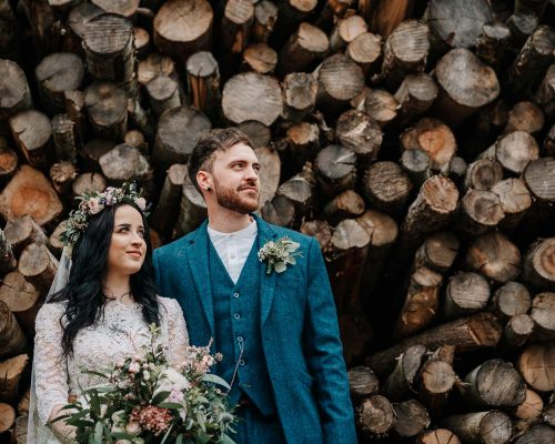 Bride & Groom in tweed suit stand in front of log pile at Cripps Barn in the Cotswolds for their wedding photographs