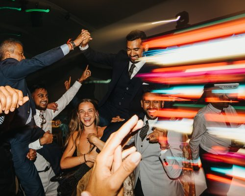 Wedding guests partying on dance floor and holding asian groom on shoulders