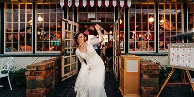 Bride in slimline wedding dress rocking out in from of victorian reception venue