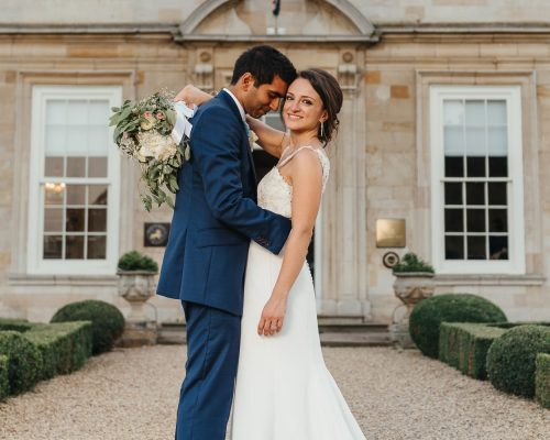 Bride and Groom embrace in front of stately home in Leicestershire