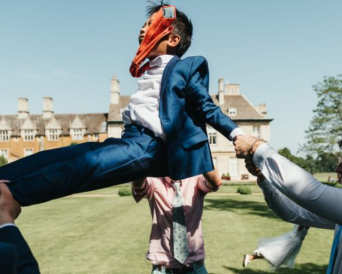 Guests swing young boy in suit playfully by his arms at Stapleford Park Wedding