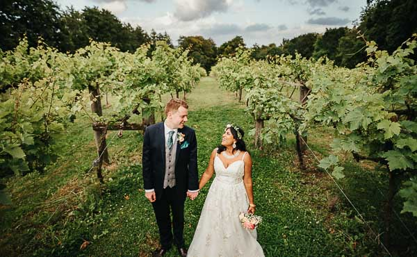 Bride and groom hold hands looking at each other lovingly in Oxfordshire Vineyard