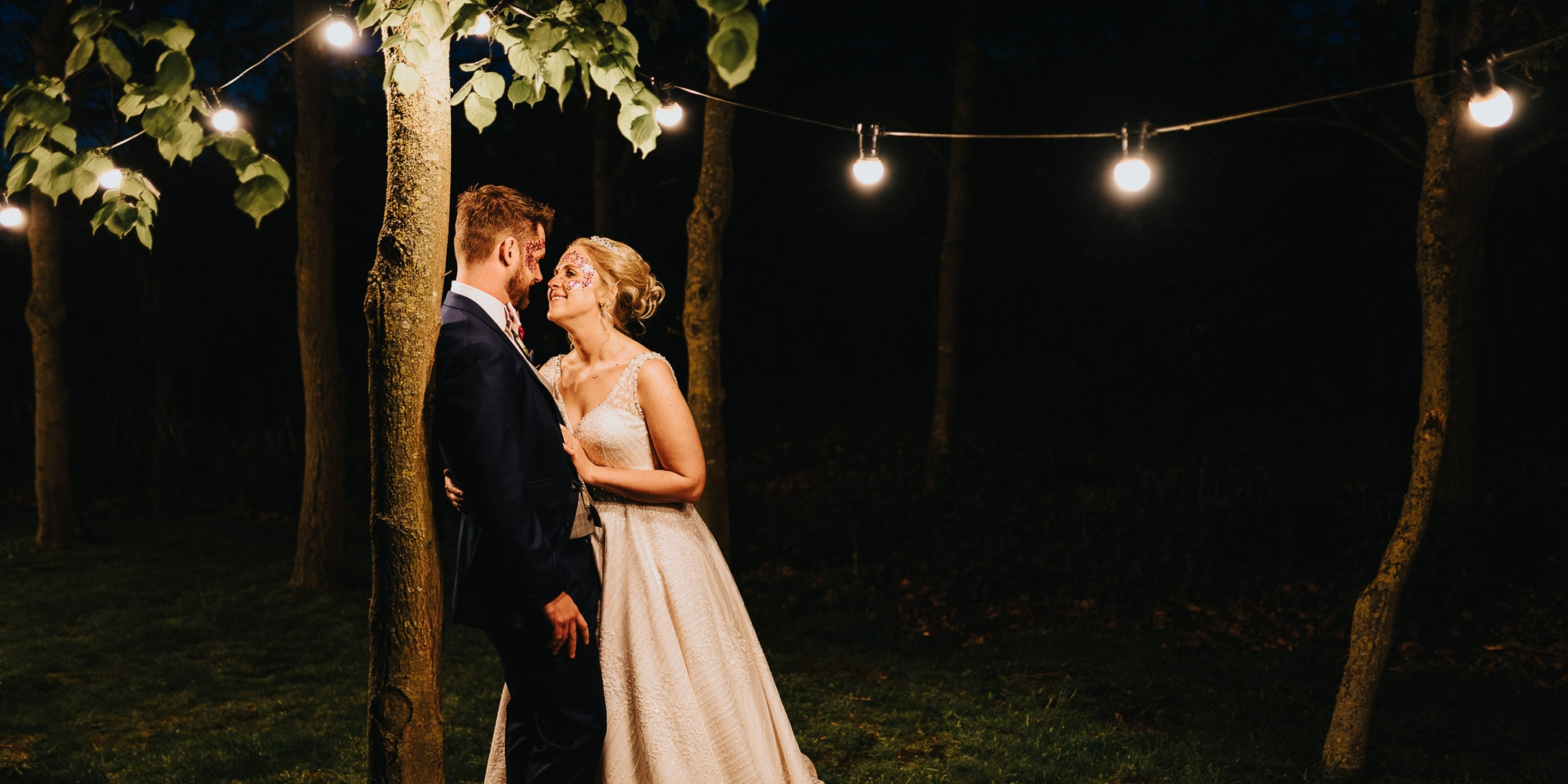 Bride and groom lean in for a kiss under festoon lights at Shustoke Barns Wedding Photography
