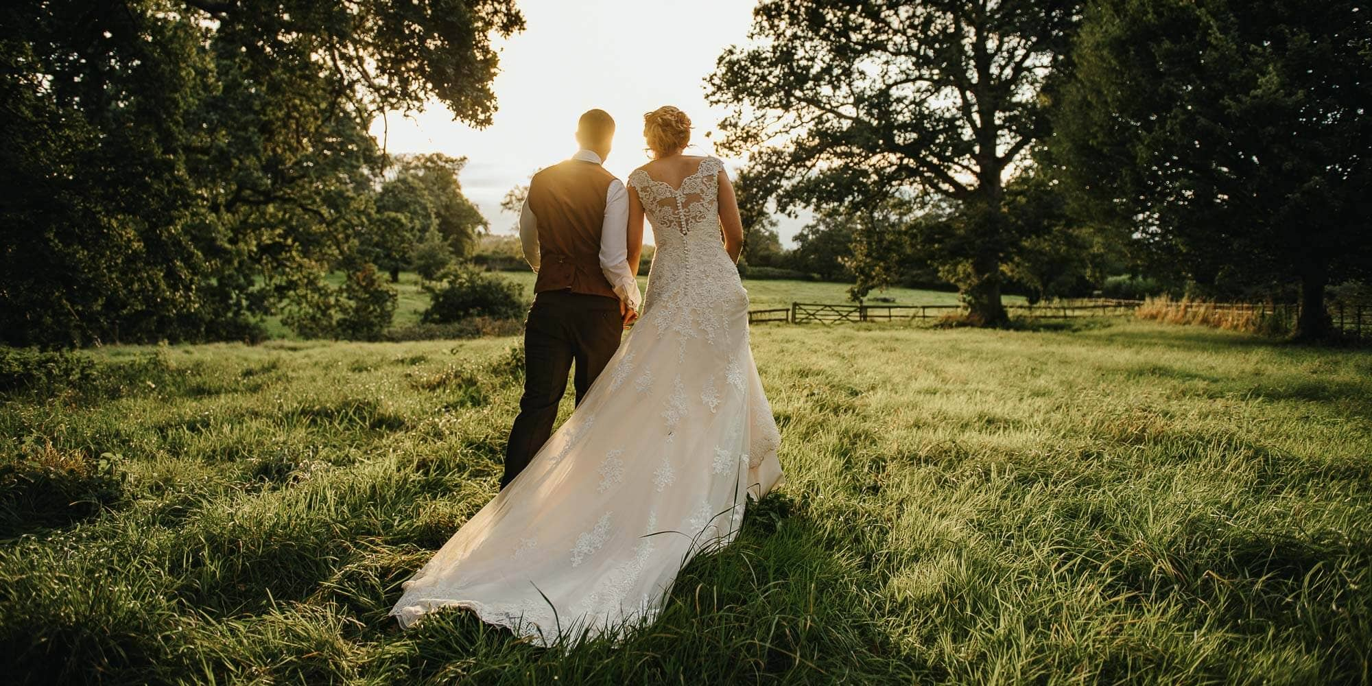 Birde and groom walk into the sunset in grassy field surrounded by trees