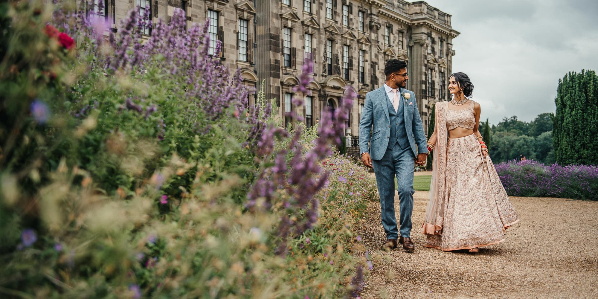 Alternative Asian married couple walk along path at Stoneleigh Abbey Wedding