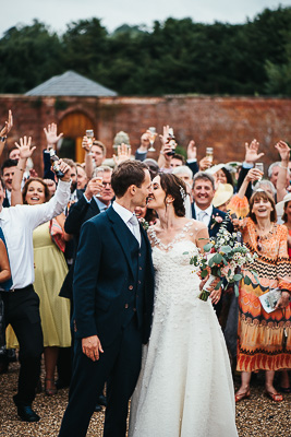 Wedding couple photographed kissing in front of their guests
